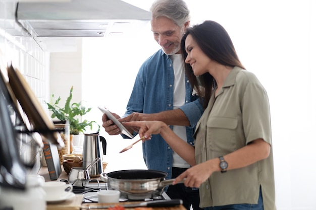 Schönes paar mit einem digitalen tablet und lächelnd beim kochen in der küche zu hause