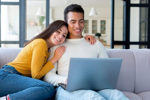 Schönes paar mit einem laptop auf dem sofa