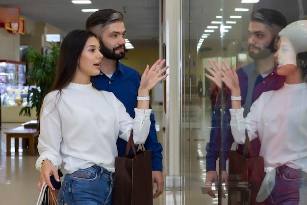 Schönes paar mit einkaufstaschen lächelnd, ein schaufenster betrachtend. einkaufen in der mall