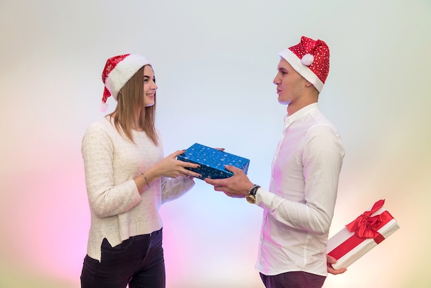 Schönes paar mit geschenkbox posiert in weihnachtsmützen im studio