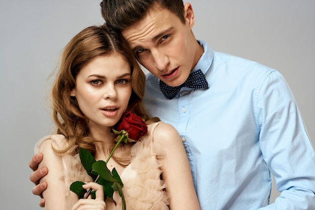 Schönes paar mit rosengeschenk, das einander umarmt