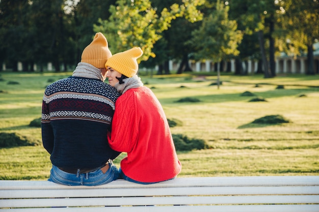 Schönes paar sitzen auf der bank zusammen, tragen warme kleidung und strickmützen, umarmen sich
