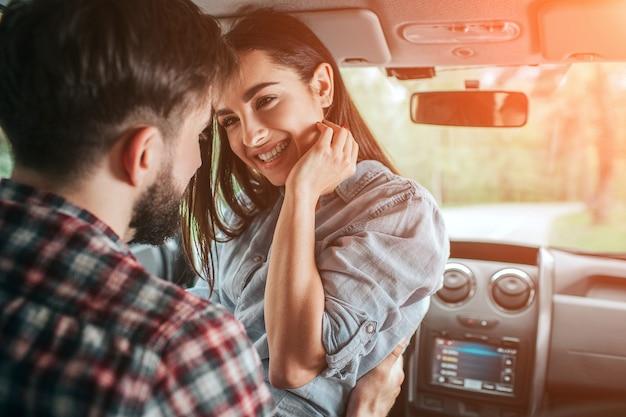 Schönes paar sitzt alleine im auto. mädchen sitzt von angesicht zu angesicht mit ihrem freund. sie hält ihre hand nahe am küken. diese dame lächelt. sie sieht glücklich aus.