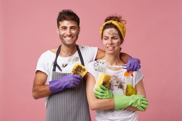 Schönes paar verliebt in die hausarbeit: attraktiver mann, der seine frau umarmt, die schmutzigen pinsel mit abneigung betrachtet. teamarbeit der familie, die über haus arbeitet. hübscher mann und frau, die möbel waschen