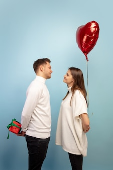 Schönes paar verliebt in herzformballon auf blauer studiowand