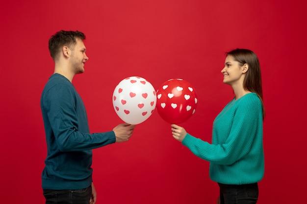 Schönes paar verliebt in luftballons auf roter studiowand