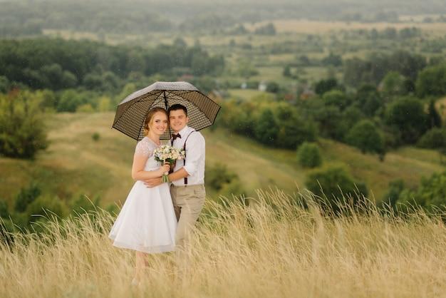 Schönes paar von jungvermählten, die einen regenschirm in ihren händen gegen schöne ansichten der grünen natur halten