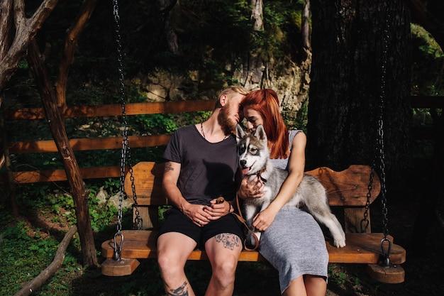 Schönes paar zusammen mit einem hund, der auf einer schaukel ruht