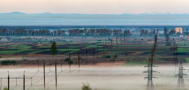 Schönes panorama der langen elektrischen hochspannungsleitungsreihen, die sich bis zum horizont durch frühlingsfelder und bäume unter dichtem morgennebel auf entferntem karpatengebirgshintergrund erstrecken.