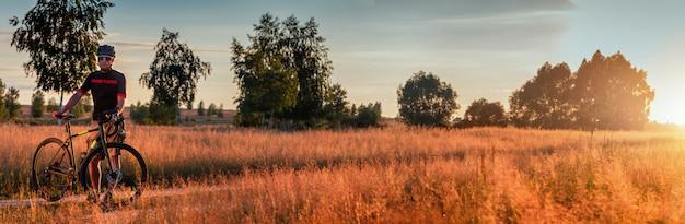 Schönes panorama eines kerls mit einem schotterrad, das auf einem weg in einem feld bei sonnenuntergang steht. schöne landschaft.