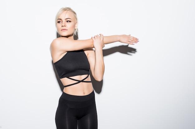Schönes passendes weibliches modell in schwarzer passender kleidung, die über weiß aufwirft