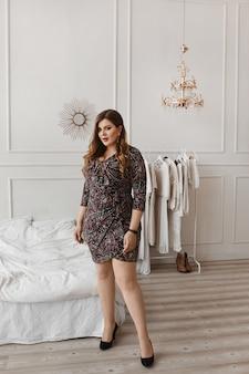 Schönes plusgrößenmodellmädchen in einem modischen kleid, das in der kamera in einem schlafzimmerinnenraum schaut. junge pralle frau mit hellem make-up und mit stilvoller frisur, die im innenraum aufwirft. xxl mode. körper positiv