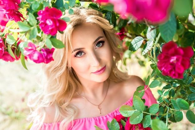 Schönes porträt blondine in den rosa rosen. nahaufnahme, make-up, verlängerte wimpern