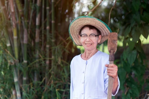 Schönes porträt der älteren frau des asiatischen landwirts des lächelns mit landwirtschaftlichen werkzeugen
