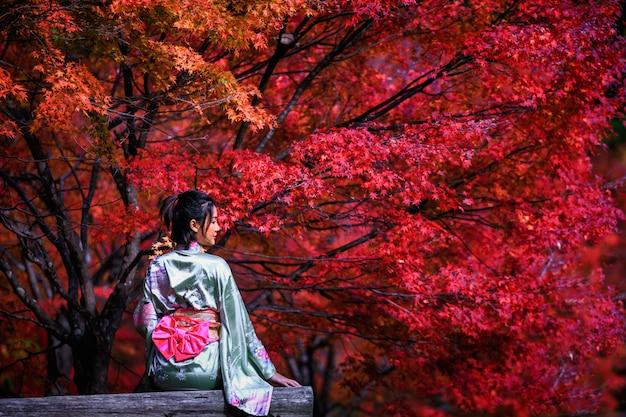 Schönes porträt der asiatischen frau, die japanischen goldkimono trägt