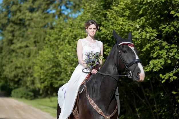 Schönes porträt der frauenbraut mit pferd am hochzeitstag