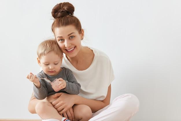 Schönes porträt der jungen mutter und des kindes, die zusammen auf weißer wand sitzen. glückliche kaukasische frau mit bündel brauner haare in weißen kleidern, die baby in ihren armen halten, aufrichtig lächelnd.