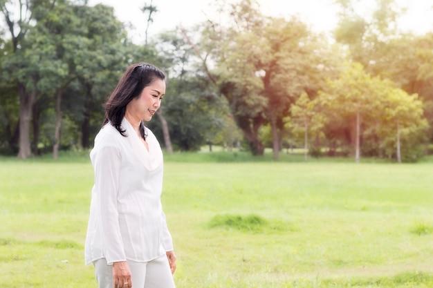 Schönes porträt der reizenden mittleren greisin, die am park lächelt und sich entspannt.