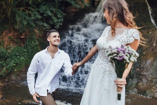 Schönes porträt des schönen und jungen bräutigams und der braut, die auf wasserfall stehen
