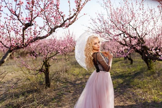Schönes porträt einer frau in einem garten von blühenden pfirsichen
