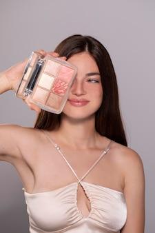 Schönes porträt einer jungen frau mit einem make-up-produkt