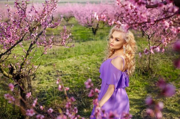 Schönes porträt eines blühenden gartens des mädchens im frühjahr, sonniger tag, pfirsichgarten