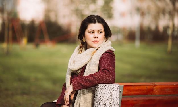 Schönes porträt eines hübschen brünetten mädchens, das lächelt und auf der bank im park sitzt