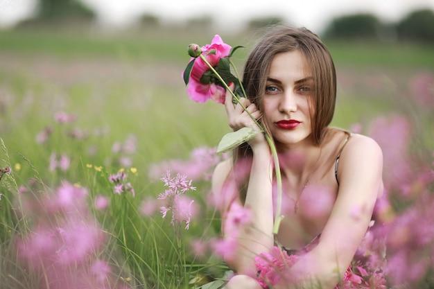 Schönes porträt eines mädchens mit rosa blumen. mädchen auf dem gebiet der blumen. burgunder-pfingstrose, landschaft