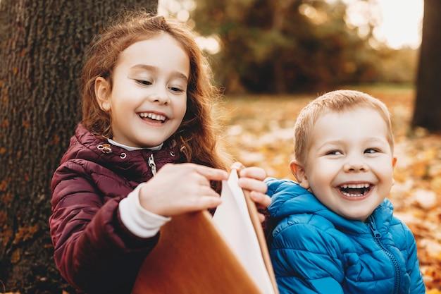Schönes porträt eines niedlichen kleinen bruders und einer schwester, die spaß am lachen haben, während mädchen ein buch öffnet, während junge draußen im park wegschaut.
