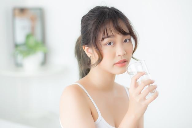 Schönes porträt junge asiatische frau kaukasier lächelnd mit ernährung durstig und trinkglas wasser.