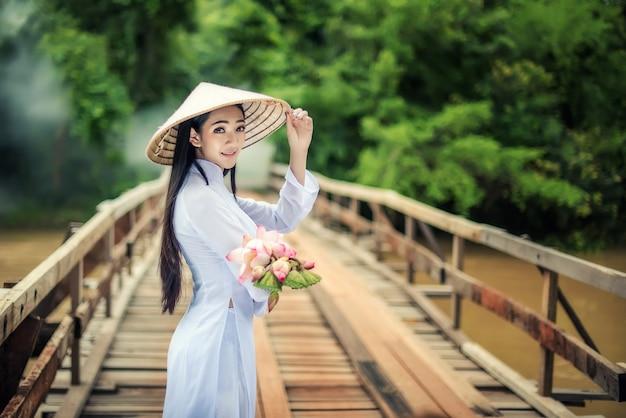 Schönes porträt von asiatischen mädchen mit ao dai walk die brücke mit lotus, vietnam-trachtenkleidkostümfrau bei vietnam.