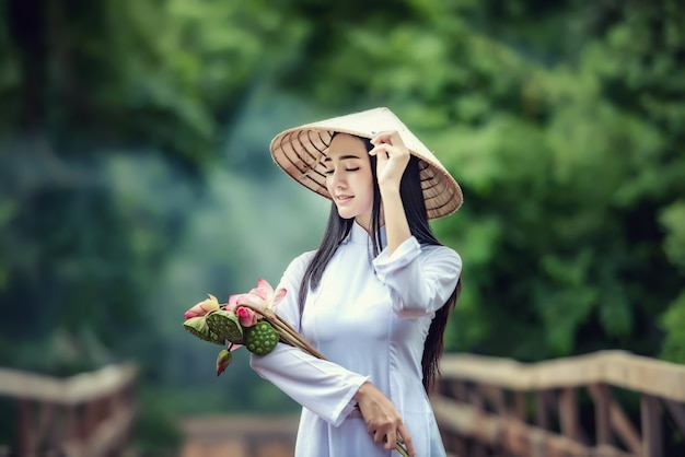 Schönes porträt von asiatischen mädchen mit trachtenkleid-kostümfrau ao-dai vietnam, weg die brücke mit lotus, bei vietnam.