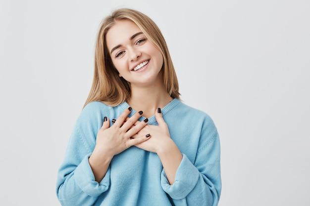 Schönes positives freundliches junges europäisches mädchen mit dem schönen aufrichtigen lächeln, das dankbar und dankbar fühlt und ihr herz zeigt, das mit liebe und dankbarkeit gefüllt ist, die hände auf ihrer brust halten