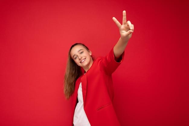 Schönes positives, glückliches, lächelndes, brünettes kleines mädchen mit trendiger roter jacke und weißem t-shirt, das isoliert über roter hintergrundwand steht und in die kamera schaut und friedensgeste zeigt