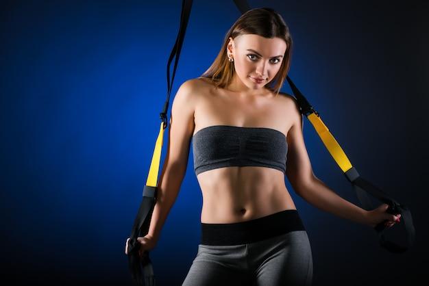 Schönes positives junges mädchen-fitnessmodell, das das festhalten an hängenden trägern aufwirft. das konzept eines sportlichen lebensstils und eines schönen körpers.