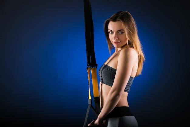Schönes positives junges mädchen-fitnessmodell, das im studio posiert, das an hängenden trägern festhält