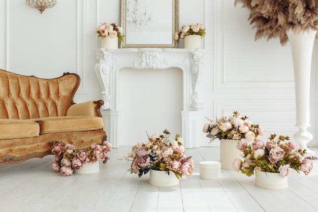Schönes provance-wohnzimmer mit braunem sofa nahe kamin mit blumen und kerzen