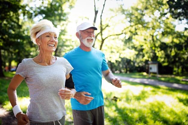 Schönes reifes paar, das in der natur joggt und gesund lebt