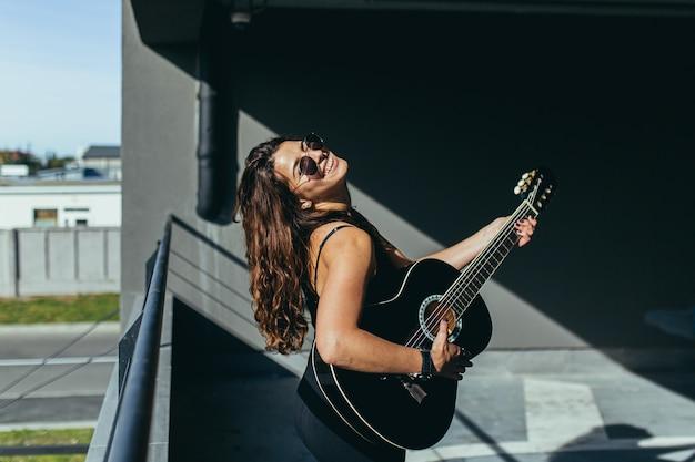 Schönes rock'n'roll-mädchen in der schwarzen brille, die mit einer schwarzen gitarre im parkplatz aufwirft