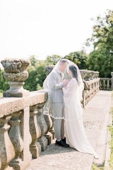 Schönes romantisches hochzeitspaar von jungvermählten, die hände nahe alten schlossgeländern umarmen und halten