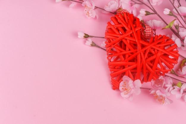 Schönes rotes herz des weidengeflechts mit rosa blumen auf einem rosa hintergrund am feiertags-februar-valentinstag