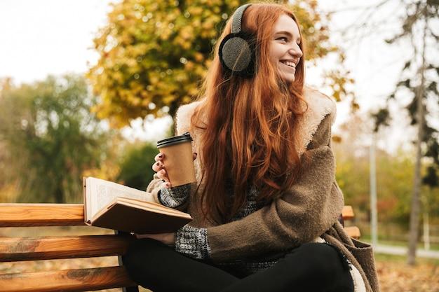 Schönes rothaariges junges mädchen, das musik mit kopfhörern hört, während auf einer bank sitzt, ein buch liest, kaffee trinkt