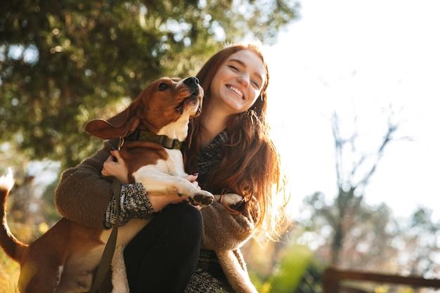 Schönes rothaariges junges mädchen, das musik mit kopfhörern hört, während sie mit ihrem hund im park spielt