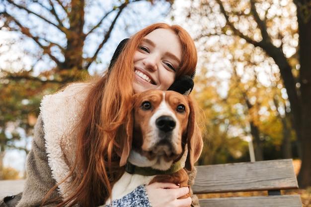 Schönes rothaariges junges mädchen, das musik mit kopfteilen hört, während es auf einer bank sitzt und einen hund streichelt