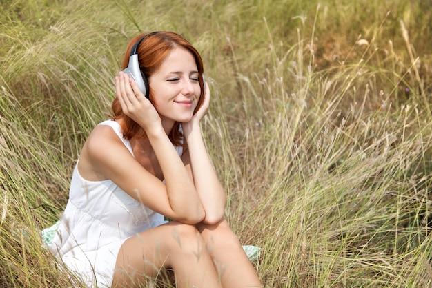 Schönes rothaariges mädchen am gras mit kopfhörern