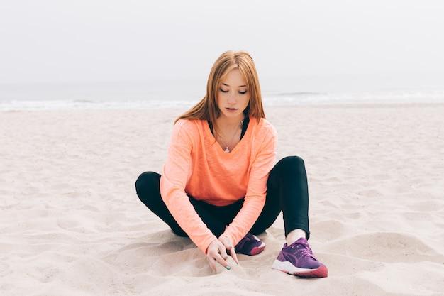 Schönes rothaariges mädchen, das auf dem strand sitzt