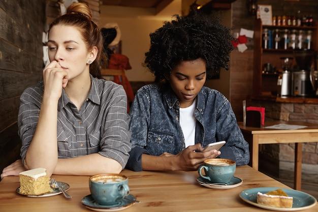 Schönes rothaariges mädchen, das besorgten blick hat und während des mittagessens mit ihrer internetabhängigen freundin im café sitzt
