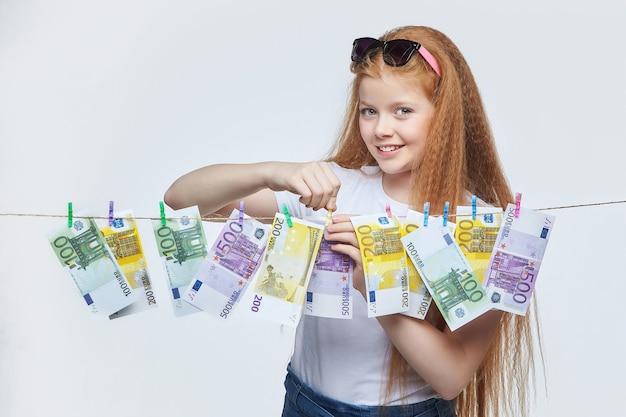 Schönes rothaariges mädchen hängt euro-banknoten an einem seil