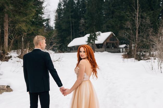Schönes rothaariges mädchen im winterkleid, das die hand eines kerls hält.