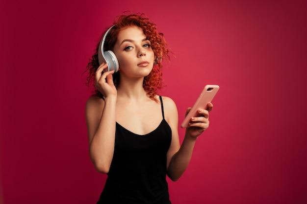 Schönes rothaariges mädchen in den großen weißen kopfhörern mit telefon in der hand hörend musik